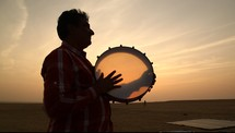 man with a tambourine in the desert