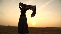 woman with a scarf dancing in the desert at sunset