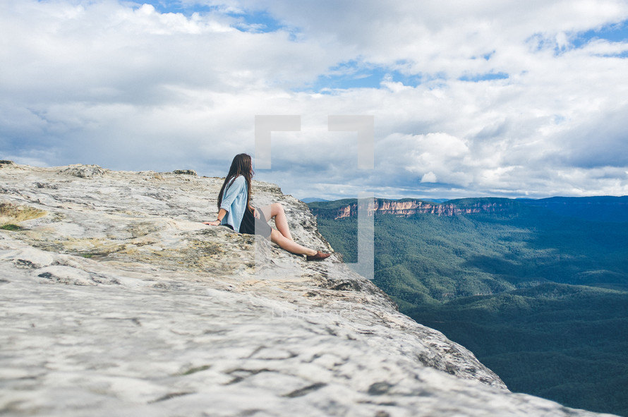 Woman sitting at the top of a mountain looking into the valley.