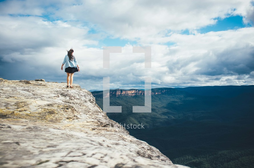 woman walking on the edge of a cliff