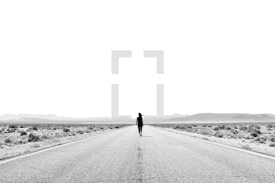 a woman walking down the middle of a desert road