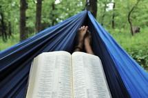 reading a Bible in a hammock