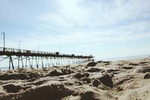 a fishing pier and sand on a beach