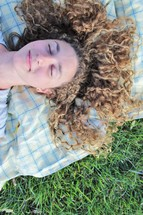 a woman napping on a blanket in the grass