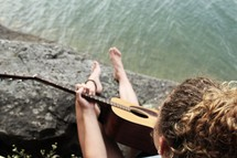 a girl playing an acoustic guitar sitting on a shore