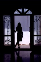silhouette of a woman standing in a doorway