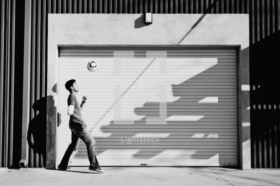 man tip toeing in front of a garage