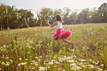 Girl playing with hula hoop in grass field