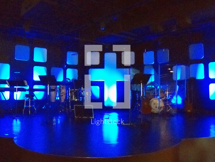 A sound stage complete with keyboards, drums, guitars all set up for a live praise and worship band to come and play before a live audience in a contemporary worship live church service. The background of the stage has a large cross and the stage is lit with blue lighting.