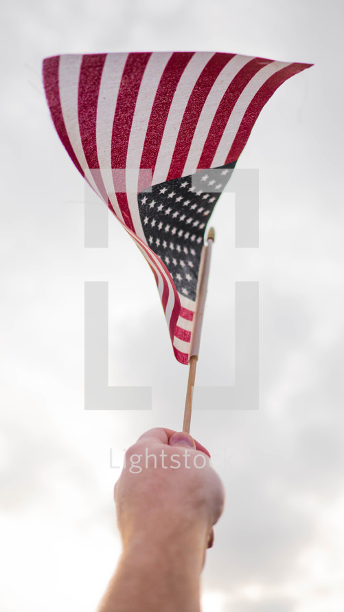 hand holding up an American flag