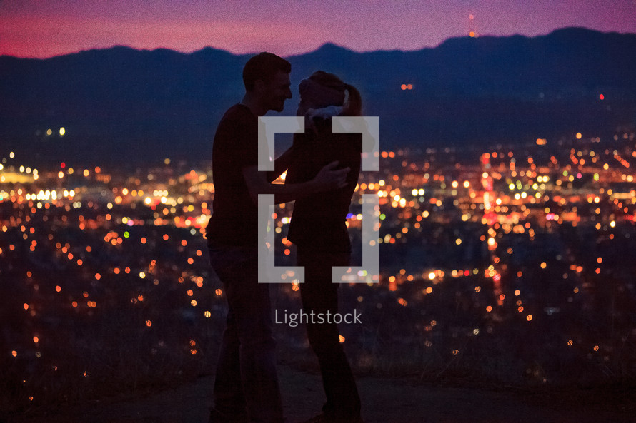 A couple in love in front of the lights from the suburbs below at night.