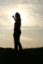 Silhouette of woman pointing at the sky.
