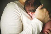father cradling a newborn