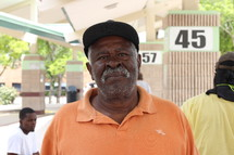 African American man in a orange shirt standing outdoors
