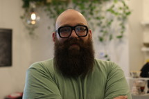 A bald man with a heavy beard and glasses.