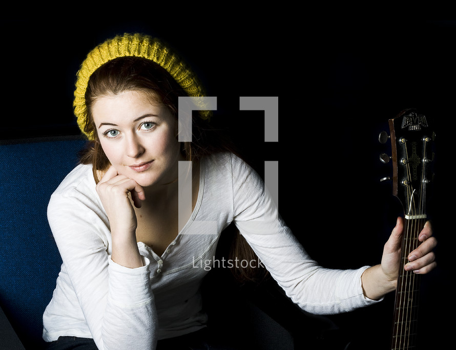 woman in a knit hat holding a guitar neck