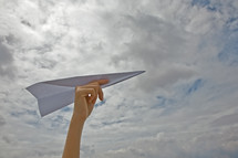 child throwing a paper airplane