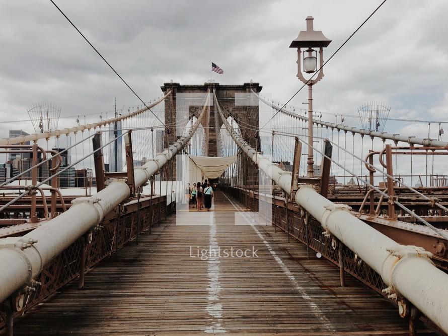 People walking on the Brooklyn bridge.