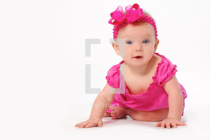 infant girl in fuchsia crawling