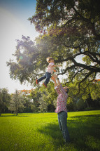 a father tossing his son in the air