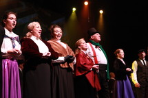 performers singing on stage - Christmas Carol