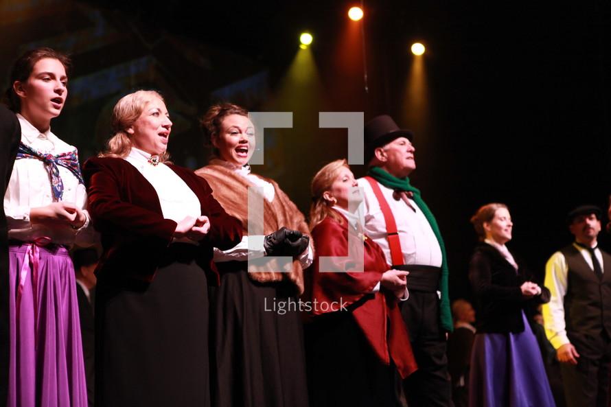 performers singing on stage - Christmas Carol
