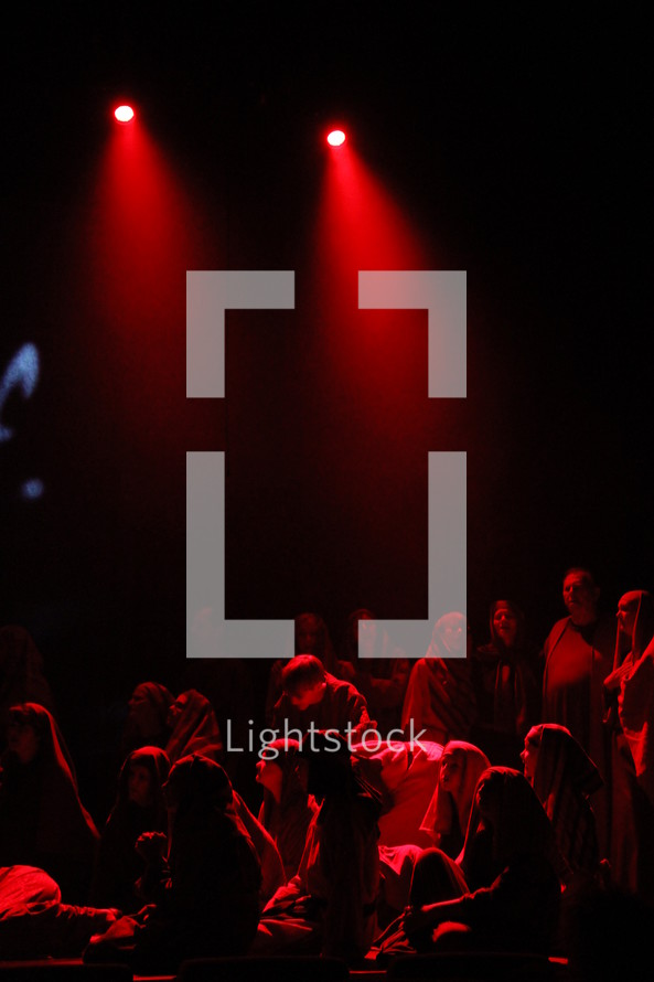 performers dressed as shepherds sitting on stage under the glow of red light