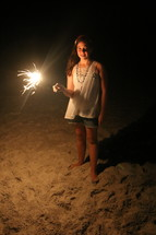 a girl holding a sparkler on a beach
