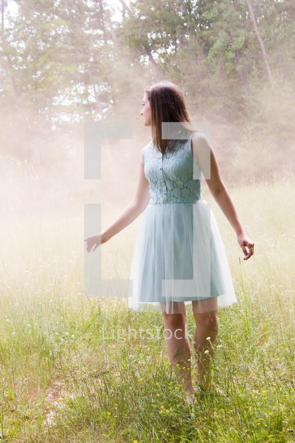 girl in a dress standing in a field