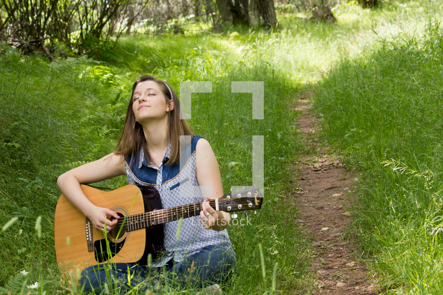 woman in a field playing her guitar