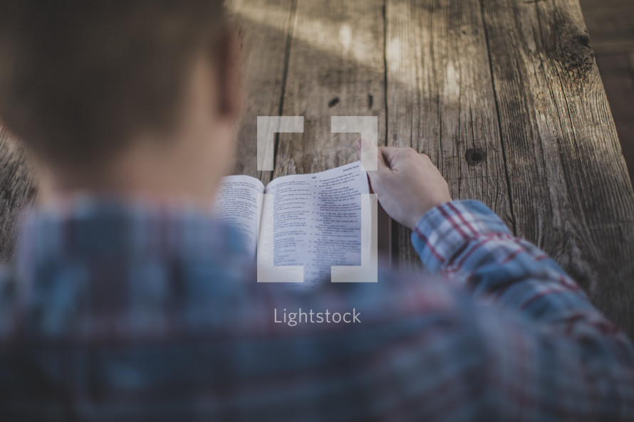 Over the shoulder view of a man reading the Bible