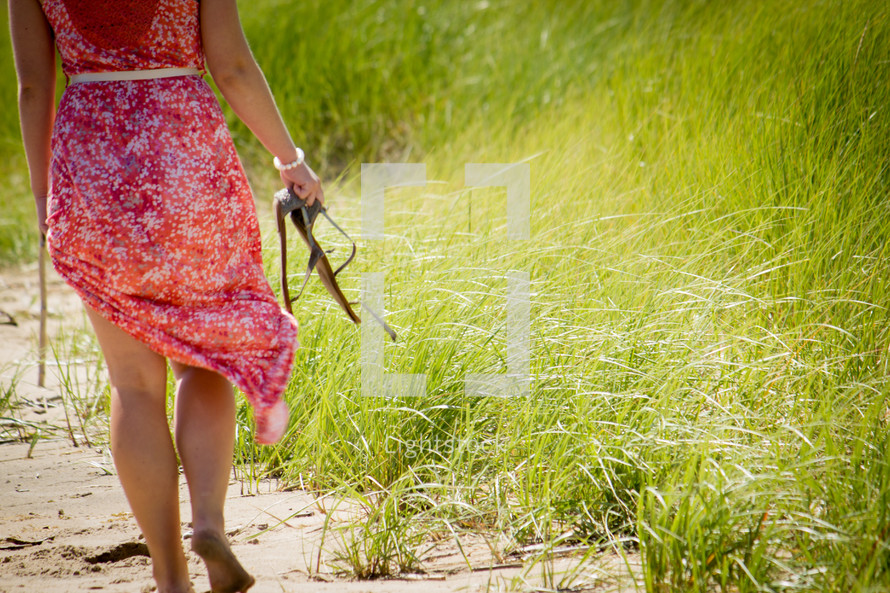 Woman carrying sandals while walking along the beach.