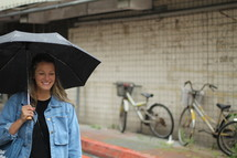 a woman walking with an umbrella down a street