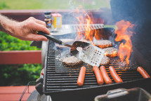 cooking hamburgers and hotdogs on a grill