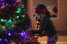 a girl decorating a Christmas tree