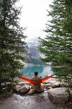 man in a hammock at a lake shore