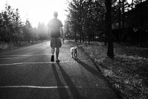 a man walking his dog on a leash at sunset