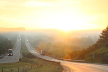 Vehicles on a highway leading into the sunset.