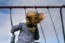 a child swinging on a swing set