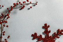red berries and snowflake ornaments on a white background