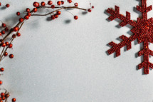 red berries and snowflake ornaments on white background