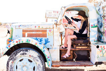 a woman sitting in an old truck painted with flowers