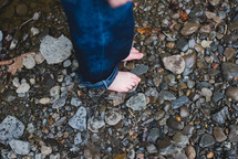a barefoot child standing on pebbles