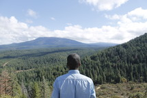 Back of a man on a hillside looking into a valley of trees.