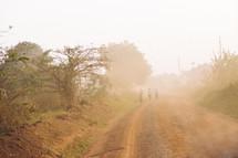 people walking down a foggy dirt road