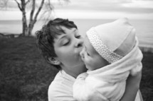 a brother kissing his baby sister