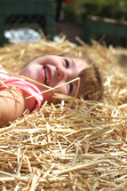 a toddler girl lying in hay