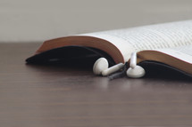 earbuds marking the page of a Bible