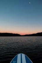paddle board on a lake at sunset