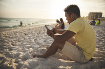 man reading a tablet on a beach
